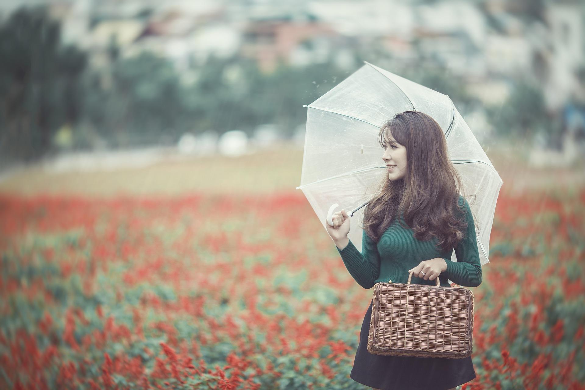 kobieta z parasolką z lnianą torebką w deszczu